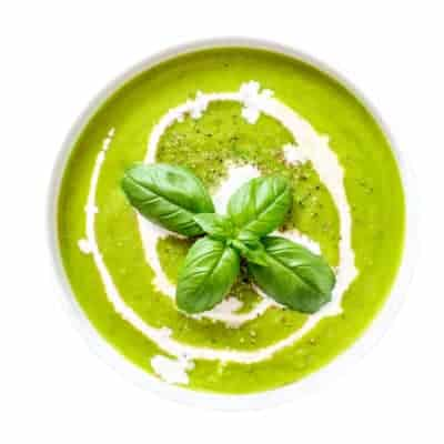 Spinach soup with cream in a bowl. Broccoli and Spinach creamy soup with croutons isolated on white background, top view. Close up. Detox healthy food