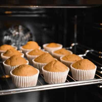 Tasty cupcakes on baking rack in oven