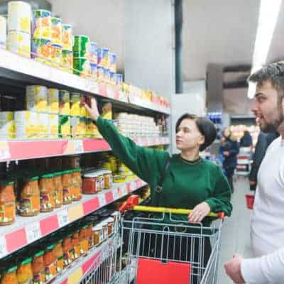 Young couples shopping for canned grocery food to save money