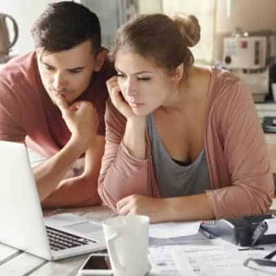 Serious man and woman sitting at kitchen table in front of open laptop computer, looking at screen with concentrated expression, focused on paying utility bills online. Family budget and finances